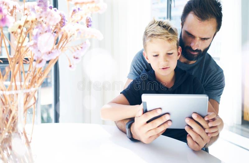Père barbu avec son jeune fils à l'aide de la tablette dans la chambre ensoleillée Papa et petit garçon jouant ensemble sur l'ord photos stock