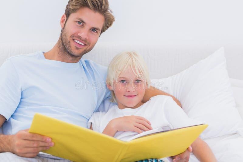 Père beau lisant une histoire à son fils images stock