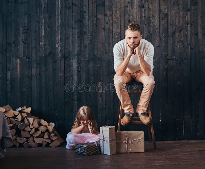 Père bouleversé et fille s'asseyant près des boîtes avec des cadeaux dans la chambre vide contre le mur en bois image stock
