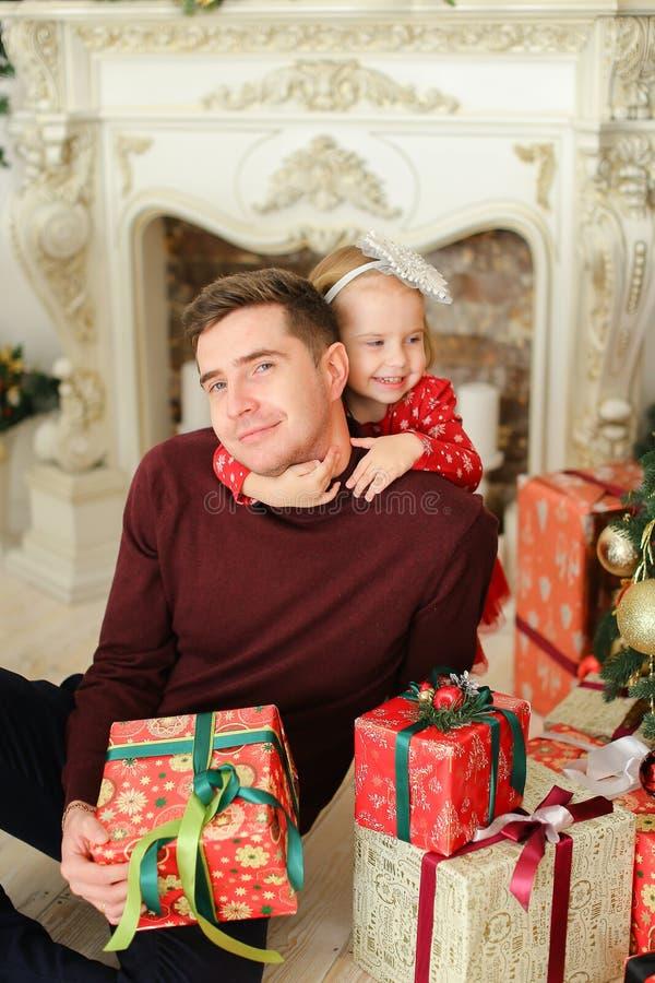 Père caucasien s'asseyant avec la cheminée décorée proche de petite fille et gardant des présents photo libre de droits