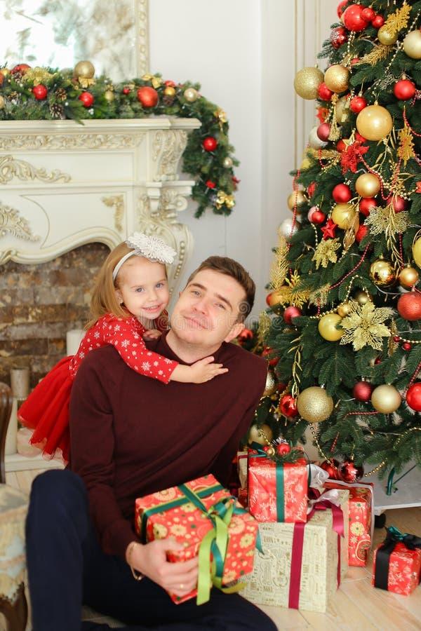 Père caucasien sittling avec la cheminée proche de petite fille et l'arbre de Noël décorés, gardant des présents photo libre de droits