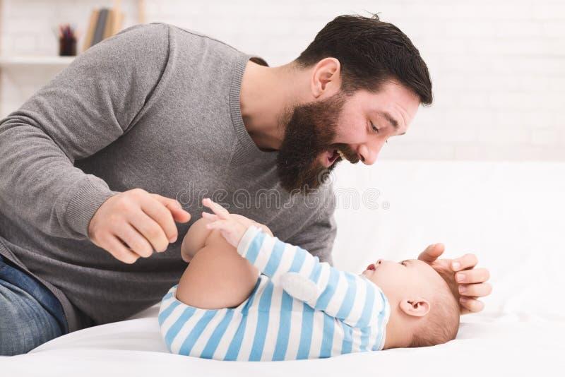 Père chatouillant et se blottissant son fils de bébé photos stock