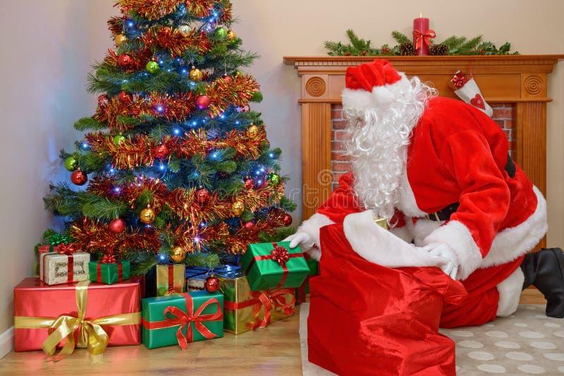 Père Christmas mettant des cadeaux sous l'arbre photos libres de droits