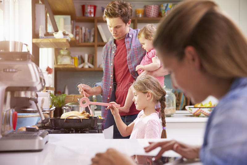 Père Cooks Family Meal tandis que la mère utilise la Tablette de Digital photos stock