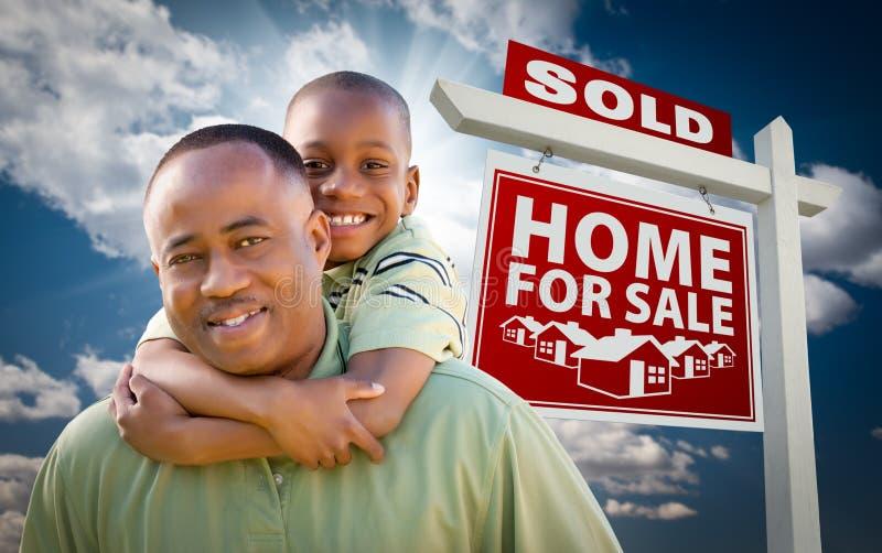 Père d'Afro-américain avec le fils devant le signe image stock
