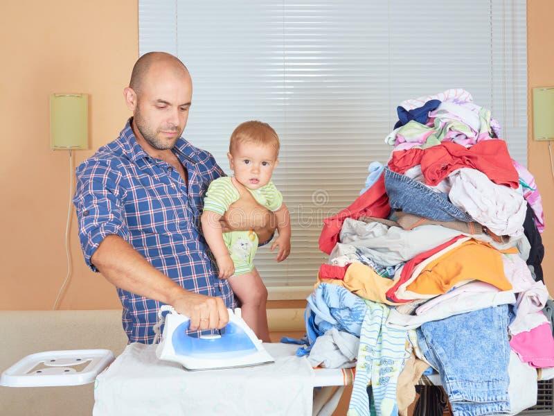 Père d'homme et fils caucasiens dans des ses mains, vêtements repassés dans photographie stock
