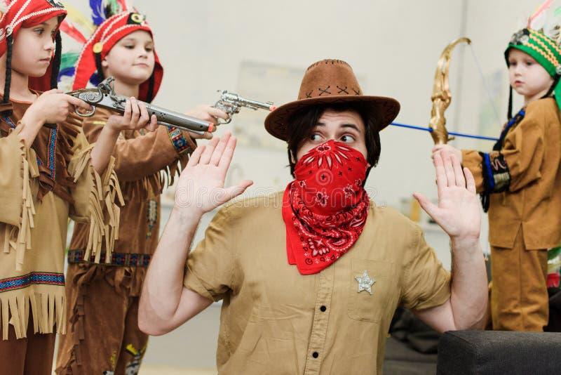 père dans le chapeau et le bandana et petits fils dans des costumes indigènes avec des jouets jouant ensemble images stock