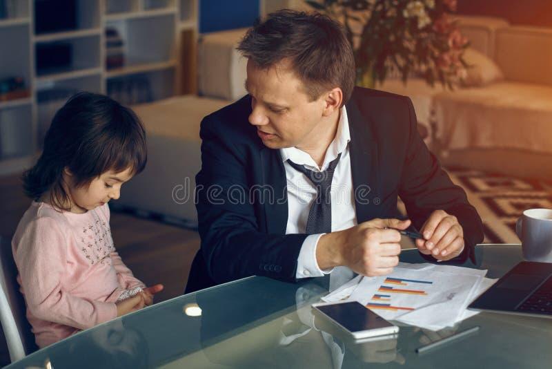Père de aide de fille travaillant à la maison images stock