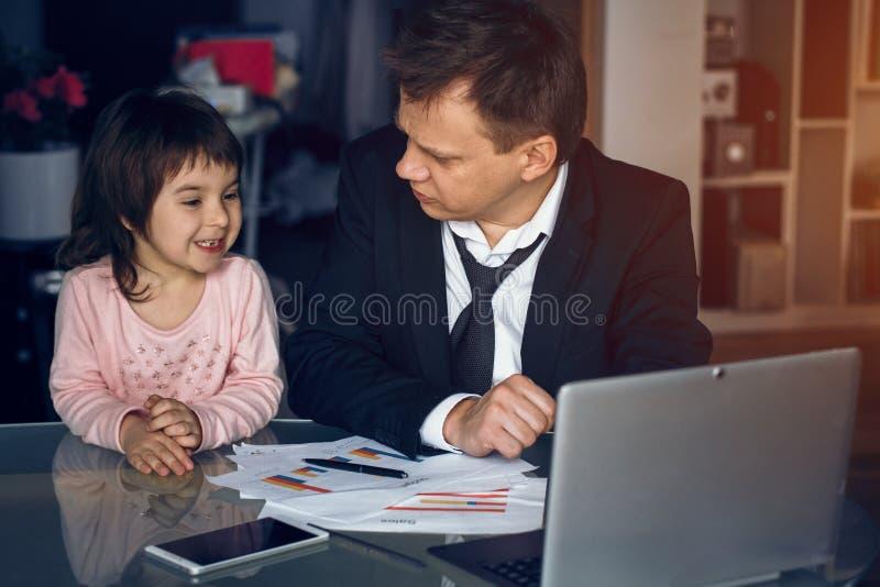 Père de aide de fille travaillant à la maison photographie stock libre de droits