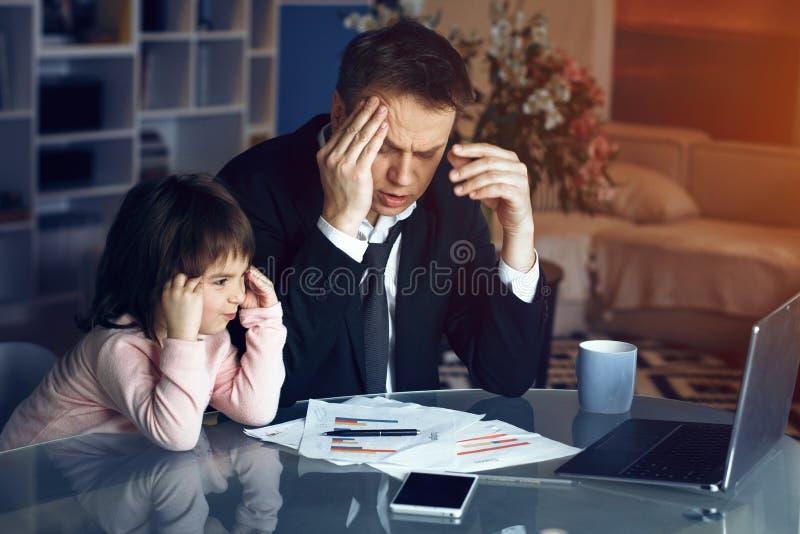 Père de aide de fille travaillant à la maison photo stock