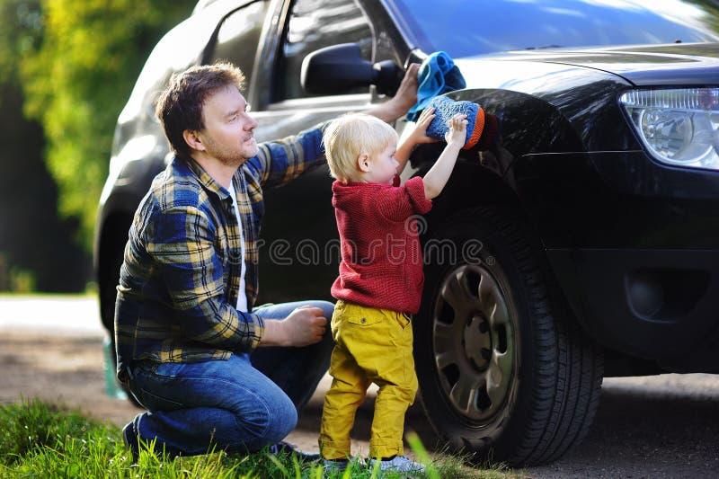 Père de Moyen Âge avec sa voiture de lavage de fils d'enfant en bas âge ensemble dehors photos stock