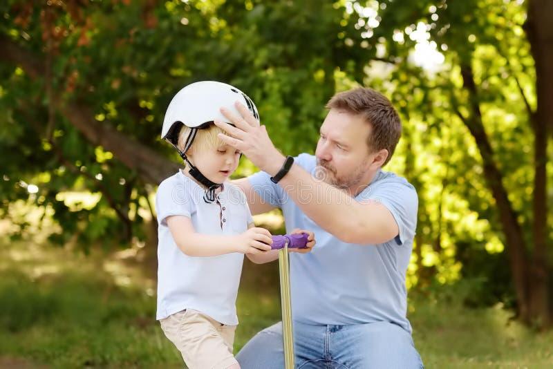 Père de Moyen Âge aidant son petit fils à mettre son casque photographie stock