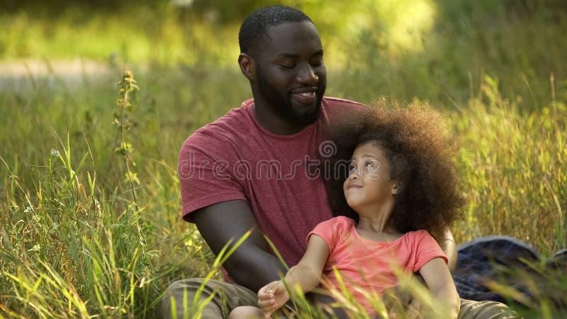 Père de parent célibataire prenant soin de petite fille prisée avec les cheveux bouclés image libre de droits