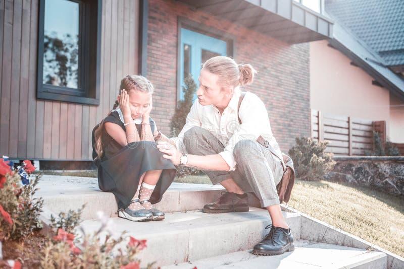 Père de soin parlant à son sentiment de fille émotif le premier jour à l'école photos stock
