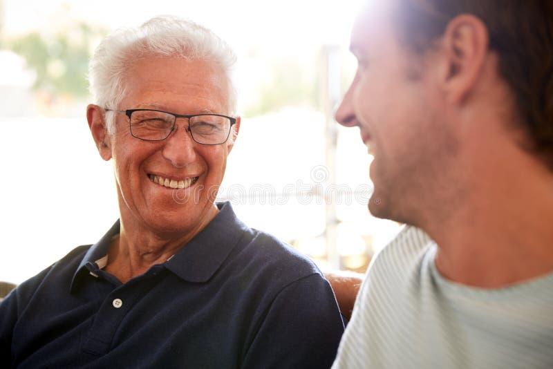 Père de sourire With Adult Son détendant sur Sofa At Home image stock