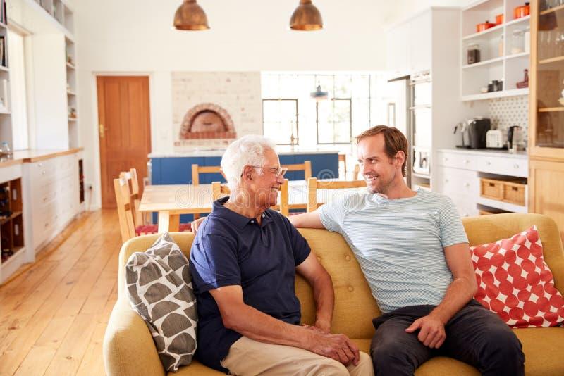 Père de sourire With Adult Son détendant sur Sofa At Home photographie stock