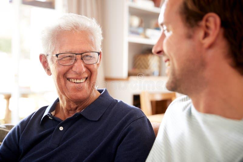 Père de sourire With Adult Son détendant sur Sofa At Home photos libres de droits