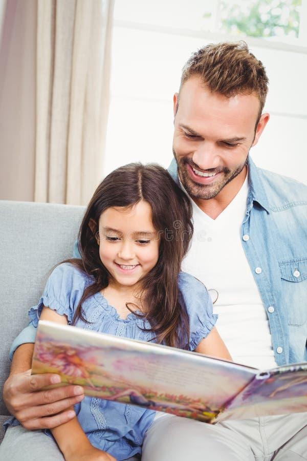 Père de sourire avec le livre de lecture de fille photos libres de droits