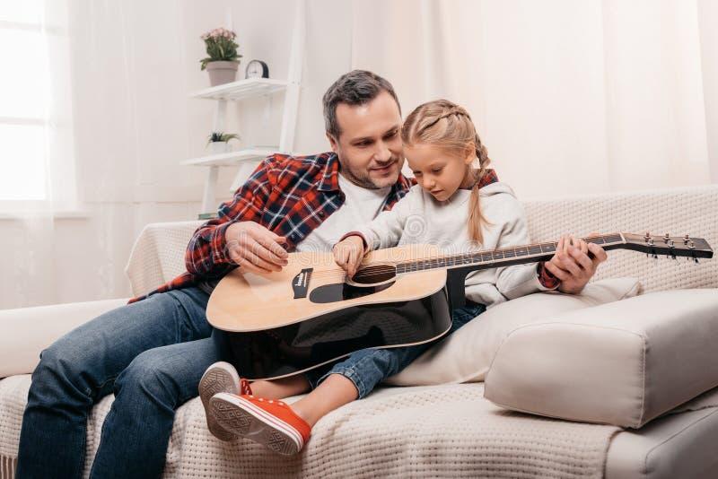 père de sourire enseignant le petit jeu mignon de fille acoustique images stock