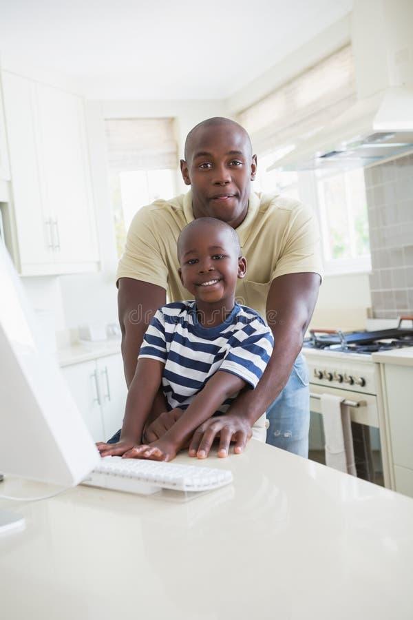 Download Père De Sourire Heureux Avec Son Fils à L'aide De L'ordinateur Photo stock - Image du enfant, home: 56484800