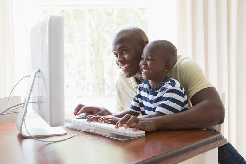 Download Père De Sourire Heureux Avec Son Fils à L'aide De L'ordinateur Image stock - Image du contenu, domicile: 56485087