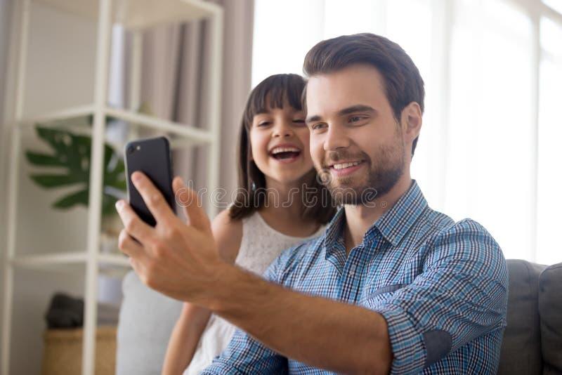 Père de sourire prenant le selfie avec la fille mignonne d'enfant sur le smartphon photos libres de droits