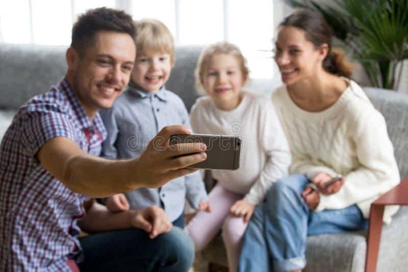 Père de sourire tenant le smartphone prenant le selfie de la famille heureuse photos libres de droits