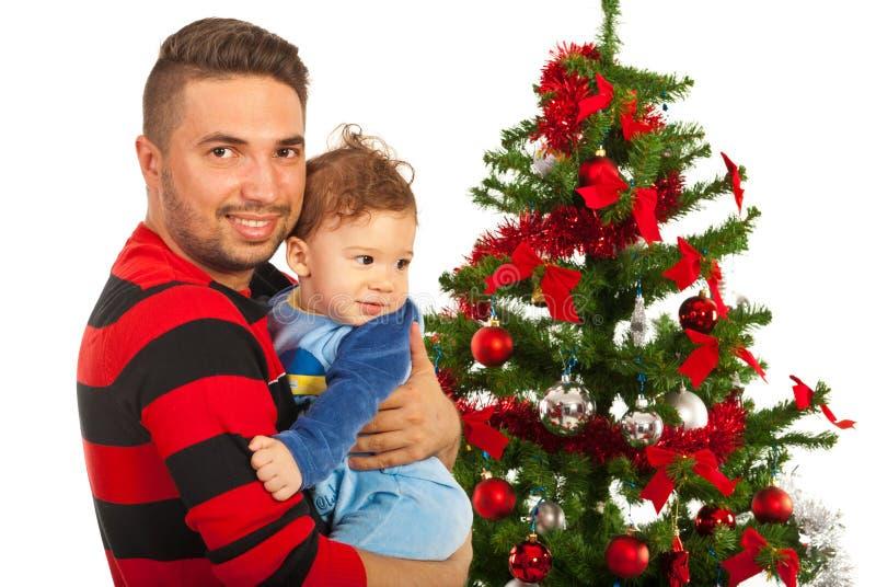 Père et bébé de sourire avec l'arbre de Noël photographie stock