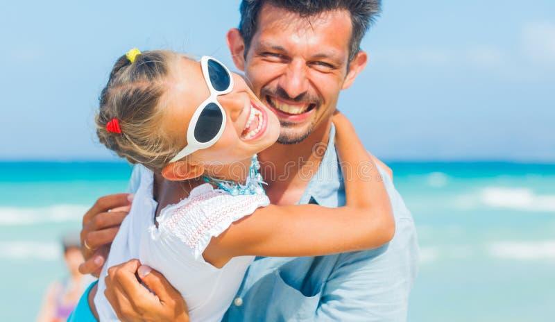 Père et descendant ayant l'amusement sur la plage images stock