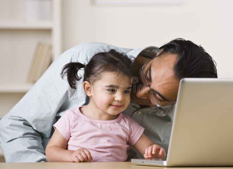 Père et descendant jouant sur l'ordinateur photo stock