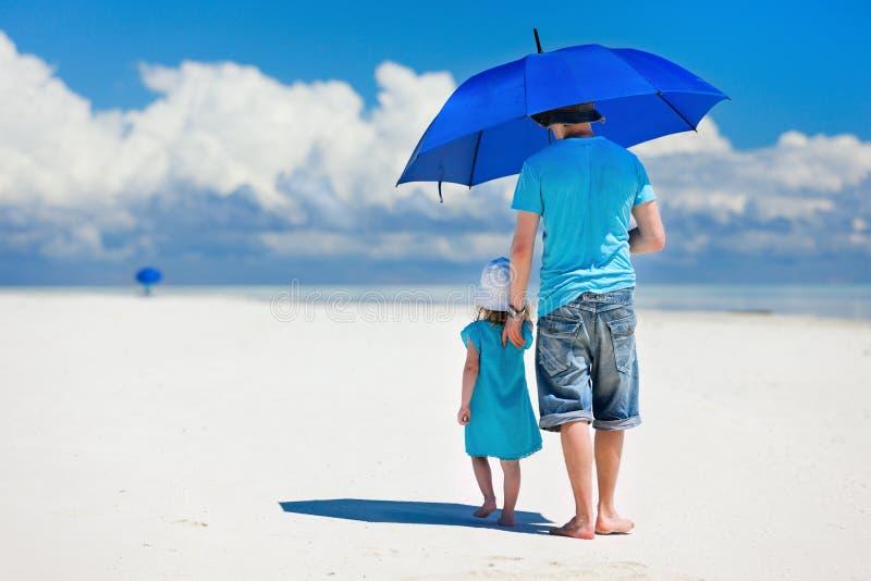 Père et descendant marchant à la plage image stock