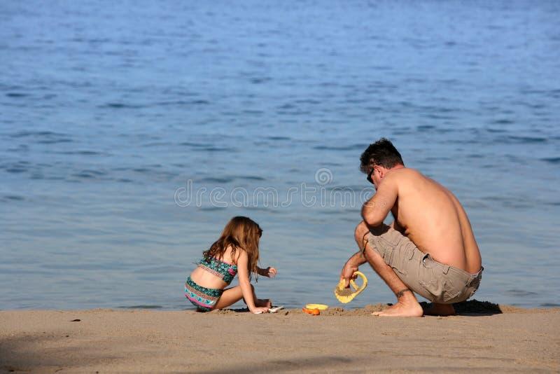 Père et descendant sur la plage photographie stock