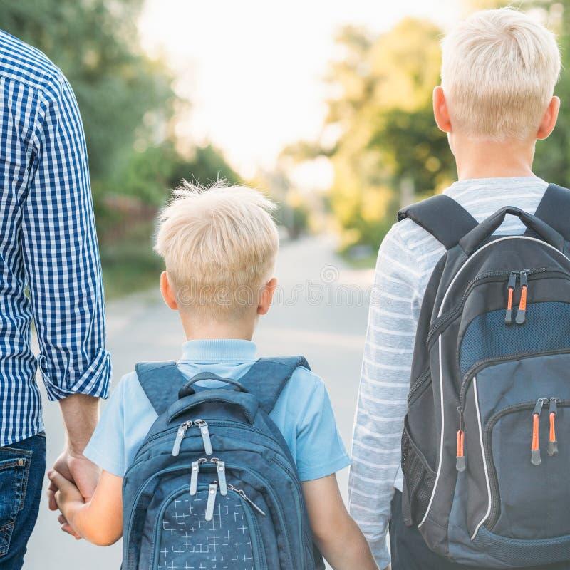Père et deux fils allant à l'école images stock