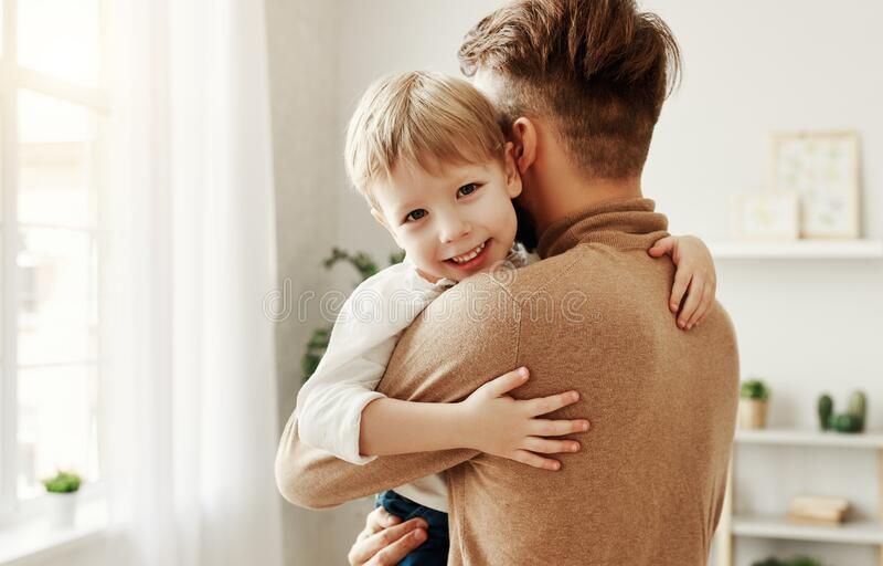 Père et enfant embrassant à la maison photographie stock