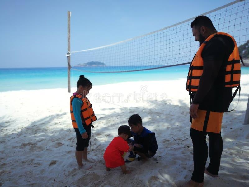 Père et enfants attendant un voyage de hors-bord en île tropicale images stock