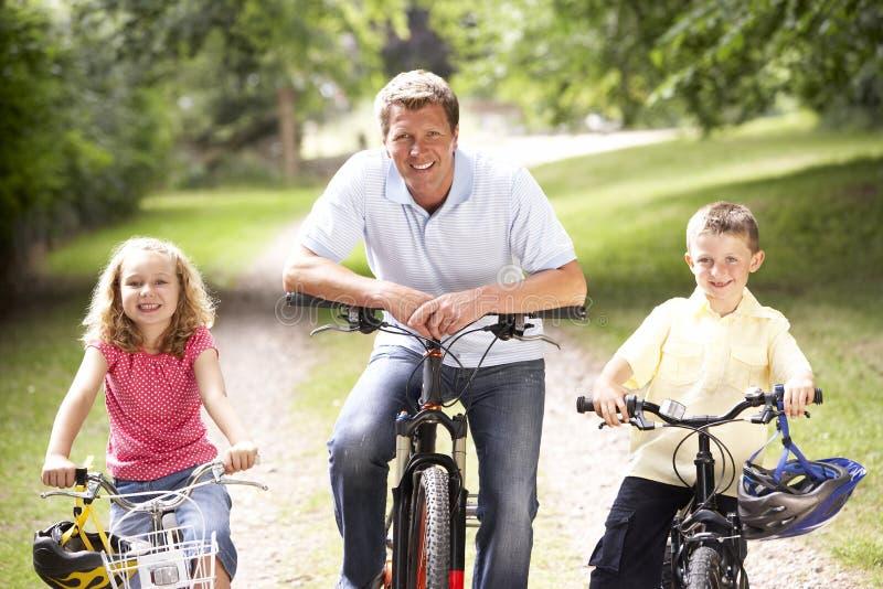 Père et enfants conduisant des vélos dans la campagne photos libres de droits