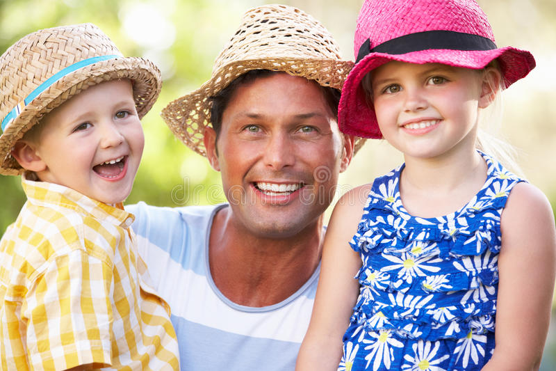 Père et enfants détendant en jardin d'été photos libres de droits