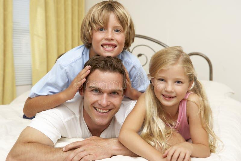 Père et enfants détendant sur le bâti à la maison photos libres de droits