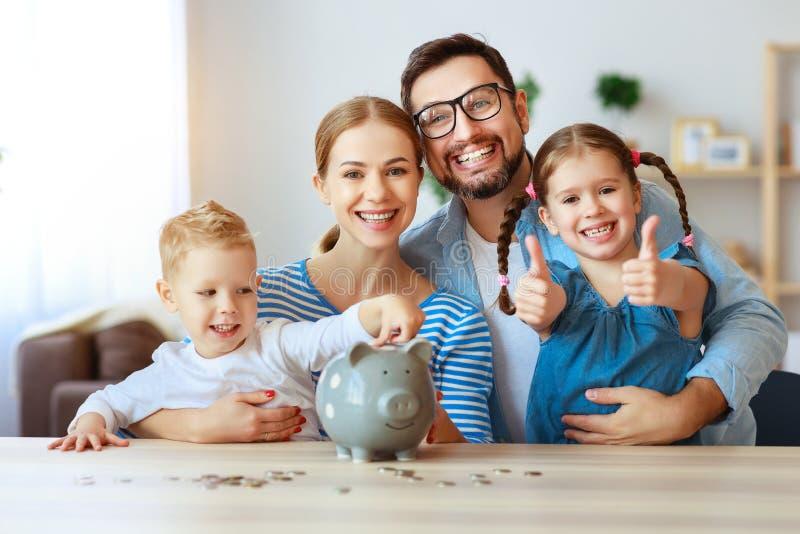 Père et enfants de mère de famille de planification financière avec la tirelire à la maison photo stock