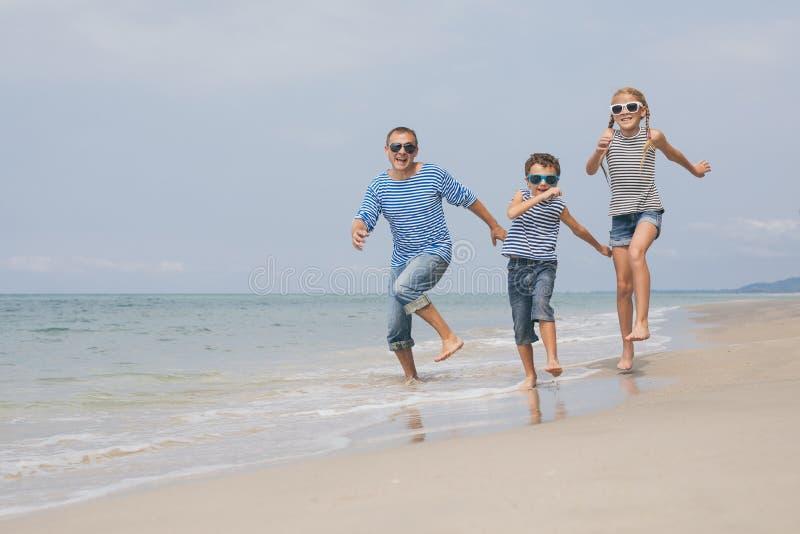 Père et enfants jouant sur la plage au temps de jour photographie stock