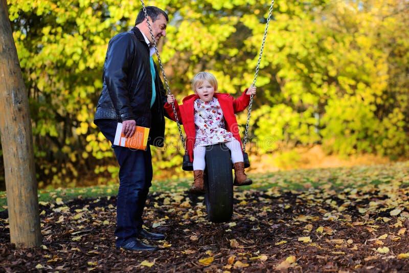 Père et fille détendant au terrain de jeu photo stock