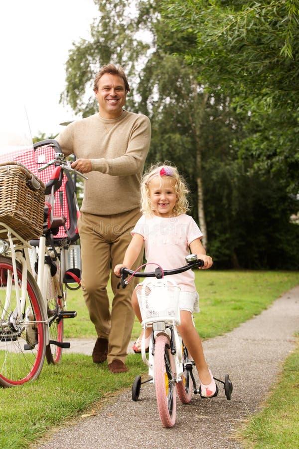 Père et fille faisant un cycle ensemble en parc photos stock