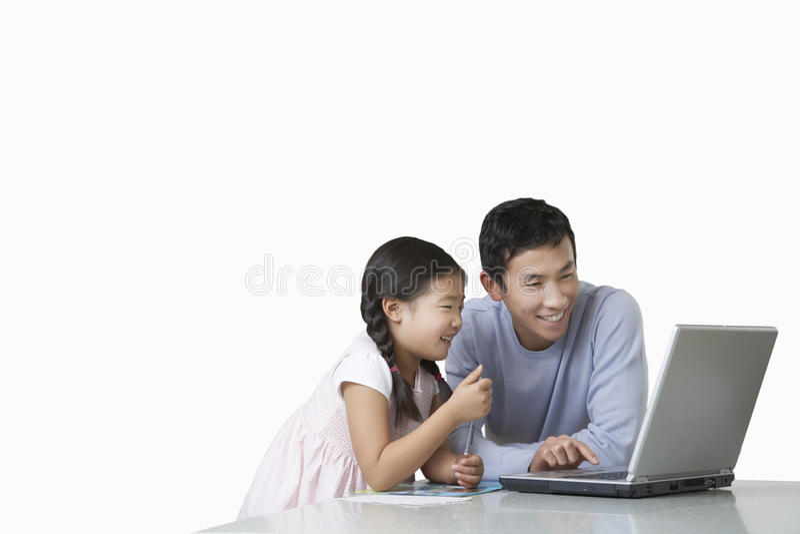 Père et fille jouant avec l'ordinateur portable sur le comptoir de cuisine images stock
