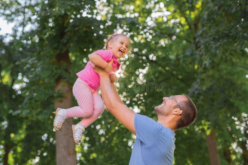 Père et fille jouant dehors en parc photos stock