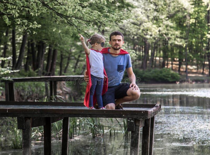Père et fille jouant un superhéros images libres de droits