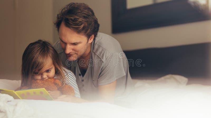 Père et fille lisant un livre d'histoire image libre de droits