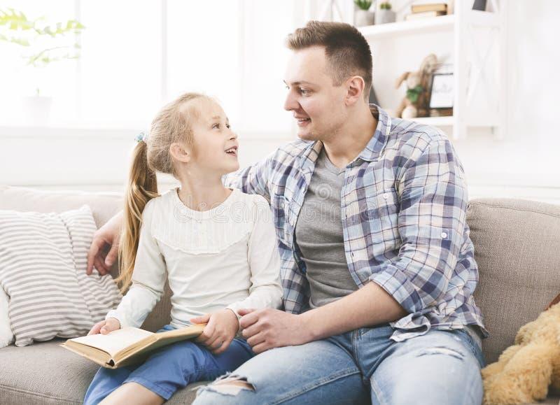 Père et fille parlant d'une histoire qu'ils ont lue image stock