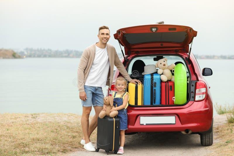 Père et fille près de tronc de voiture avec des valises sur la rive photos libres de droits