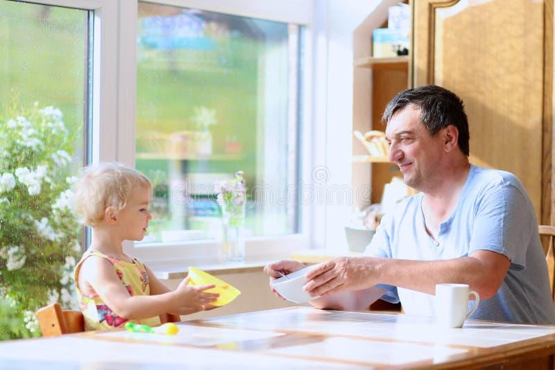 Père et fille prenant le petit déjeuner photographie stock
