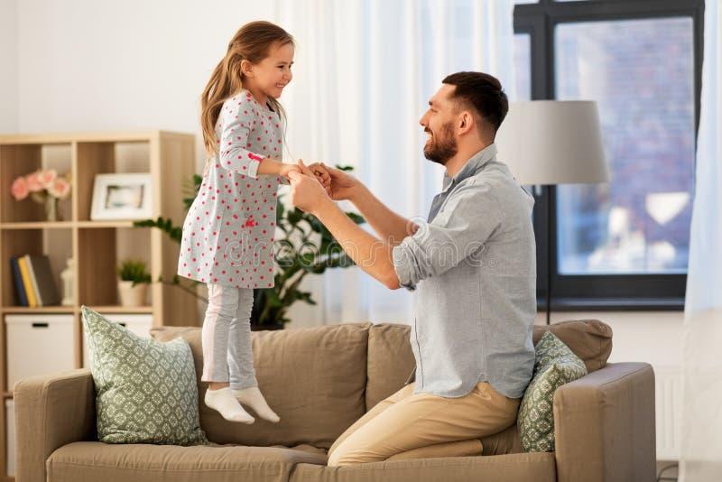 Père et fille sautant et ayant l'amusement à la maison images libres de droits